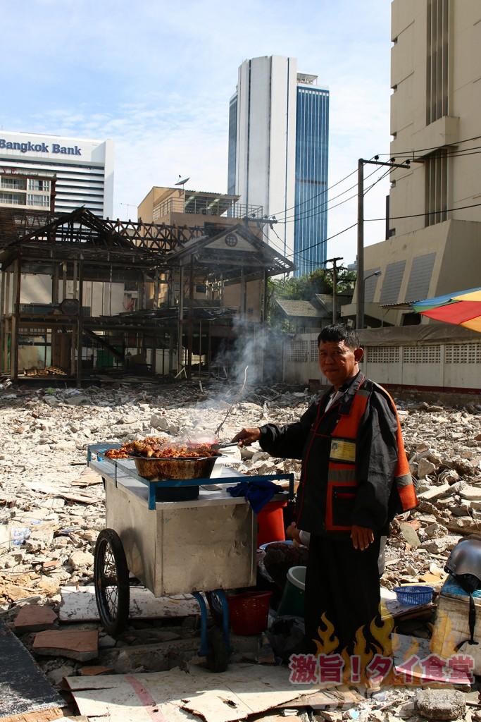 瓦礫の上で豚を焼くバイタクの運転手